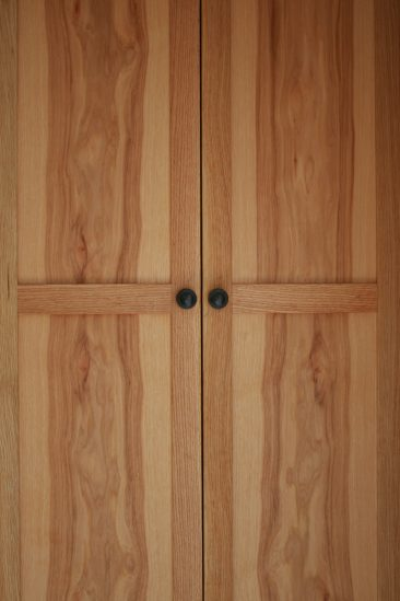 Bookmatched hickory door panels on a tall storage cabinet.